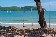 Balanços de madeira sós na frente do mar azul Imagens de Stock