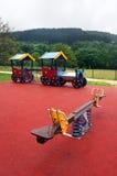 Balancê e trem no campo de jogos para crianças Imagens de Stock Royalty Free