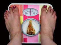 Balance 1. Woman's feet on a balance with a piece of cake stock images
