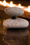 Balance. Stones balanced with candles at background Stock Photography
