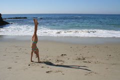 Balance. Girl doing a handstand on the ebach Royalty Free Stock Image