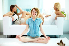 Balance. Girl in pose of lotus sitting on the floor with two friends relaxing on sofa at background Royalty Free Stock Photography