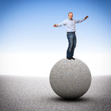 Balance. Caucasian man try to balance on concrete ball Royalty Free Stock Photo