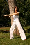 Balance. A young woman executing a stretch move while standing in a park, exercising Stock Photography