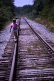 Balance. Girl walking on railroad track royalty free stock photo