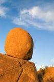 Balance. A large spherical boulder balances on another rock stock image