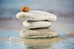 Balance. Small red stone on top of the pyramid of pebbles Stock Photos