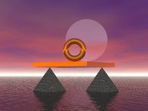 Balance and Alignment. Golden ring in the sea aligned with the moon balanced on pyramids Stock Photo