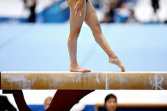Balance Beam. Legs of a gymnast are seen during an exercise on the balance beam apparatus Royalty Free Stock Images