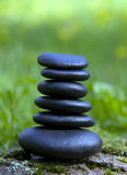 Balance. Black zen rocks stacked,on tree bark,in a meadow Royalty Free Stock Photography