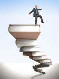 Balance on books. Man try to balance himself on 3d books pile Stock Photography