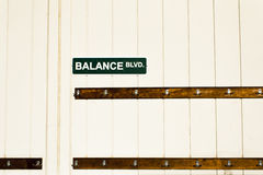 Balance Boulevard Street Sign above Clothes Hooks Stock Images