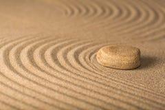 Zen garden with raked sand and a smooth stone. Balance calm concentration garden art harmony line stock photo