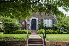 Balance a casa com chapa da bandeira americana na porta da rua arqueada e em ajardinar bonito e proveja ir Fotos de Stock Royalty Free