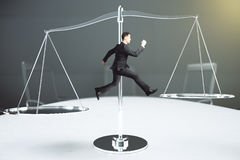 Balance concept with businessman tries to keep his balance on th Stock Photo