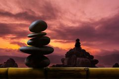 Balance Concept between of Life and work present by Natural Zen. Rock Stack on Bamboo Wooden, Sunrise or Sunset Sky as background royalty free stock photo