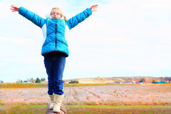 Balance. A cute little blond 9 year old girl wearing glasses and a warm blue winter hoody coat and boots standing balancing on a log. Farmland in the background Royalty Free Stock Photo