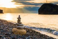 Balance at dawn - close-up of a pyramid of white stones. On a pebble beach royalty free stock photos