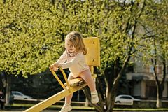 Balance, equilibrium, harmony. Girl sit on seesaw on sunny day. Kid on teeter totter outdoor. Child have fun on playground. Childhood, activity, lifestyle royalty free stock photo
