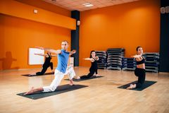 Balance exercise, female yoga group in action. Training with instructor, workout in gym. Yogi indoor Royalty Free Stock Images