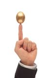 Balance a Golden Egg. Golden Egg Balanced on the Index Finger of a Man Royalty Free Stock Photos