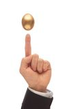 Balance the Golden Egg. Golden Egg Suspended Above a Man's Hand with the Index Finger Pointing Up Stock Image