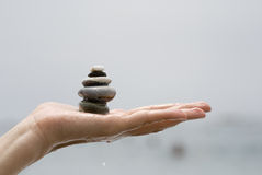 Balance on hand. One hand holds stones in balance Royalty Free Stock Images