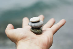 Balance on hand. One hand holds stones in balance Stock Photo