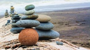 Balance and Harmony. Rounded stones stacked on a remote beach log Stock Images