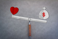 Balance between heart and money. Balance between heart (love) and money  design / Love is more valuable than money concept Stock Photo
