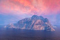 Balance a ilha da montanha no oceano sob o céu do crepúsculo Imagem de Stock