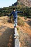 Balance of Life. A young Indian man trying to balance himself while walking on a cement beam Stock Images