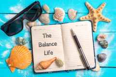 The balance life text in note book with Few Marine Items. The balance life text in note book with Beach Accessories and Few Marine Items On Blue Wooden Plank stock photography