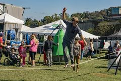 The Balance Line. Roanoke, VA – October 13th: A young man walking on the balance line at the annual GO Outside Festival at the River's Edge Park located in royalty free stock images