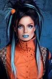 Balance a menina com bordos azuis e o penteado punk que inclinam-se contra o grun Fotos de Stock