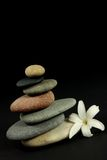 Balance of nature. Seven pebbles pyramid in staggered rows, with a white flower, over black Royalty Free Stock Photos