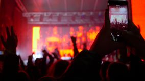 Balance o evento, formas escuras dos fãs que saltam e que acenam as mãos que gravam no telefone celular da música ao vivo do dese video estoque