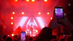 Balance o feriado, multidão de povos com os artistas fotografados telefone celular da música na fase video estoque