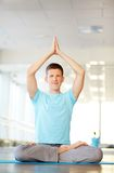 Balance. Portrait of young man doing yoga exercise in gym Royalty Free Stock Photography
