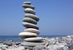Balance a pyramid of smooth stones on the background of the sea Stock Photography