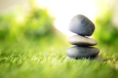 Balance with a pyramid of stone on fresh nature green grass , spa meditation or well-being with zen concept. Balance with pyramid of stone on fresh nature green royalty free stock photography