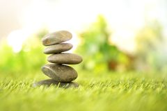Balance with pyramid of stone on fresh nature green grass , spa meditation or well-being with zen concept. Balance with a pyramid of stone on fresh nature green stock photos