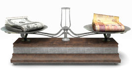 Balance Scale Comparison. An old metal and wood two pan balance scale comparing a pile of dollar bills and a pile of south african rand on an isolated white Royalty Free Stock Photography