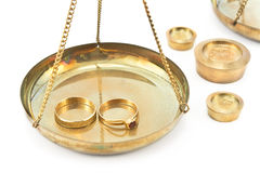 Balance scales with golden wedding rings Royalty Free Stock Photo