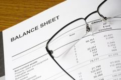 Balance sheet. Of a financial report with spectacles Stock Photos