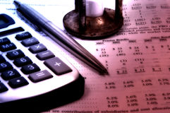 Balance Sheet. Photo of a Calculator, Pen and Hour Glass With Color and Blur Effect Stock Image