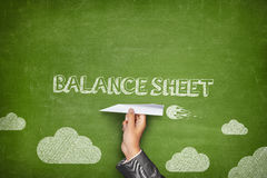 Balance sheet concept on blackboard with paper. Balance sheet concept on green blackboard with businessman hand holding paper plane Stock Photography