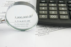 Balance sheet with magnifier and black calculator Stock Images