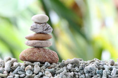 Balance stone on pile rock with garden background. Balance stone on pile rock with garden background for concept of Zen and spa Royalty Free Stock Photography