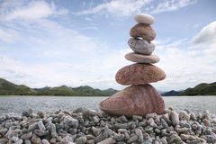 Balance stone on pile rock with river background. Balance stone on pile rock with river background for concept of Zen and calm Royalty Free Stock Image